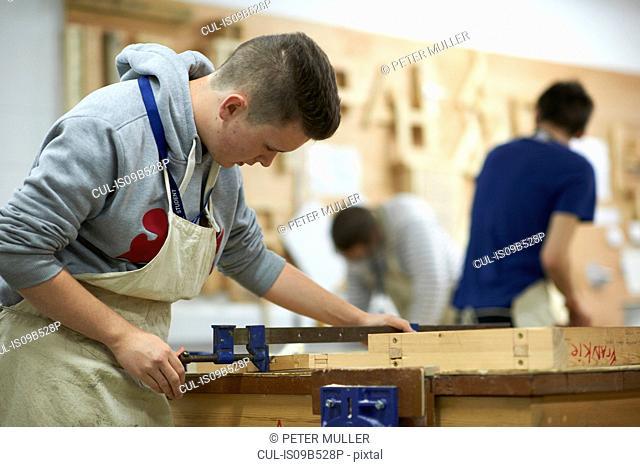 Male teenage carpentry student adjusting wood clamp in college workshop
