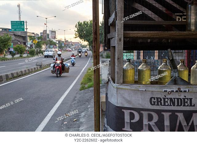 Yogyakarta, Java, Indonesia. Gasoline for Motorbikes is Sold in Recycled Liquor Bottles at Roadside Stands