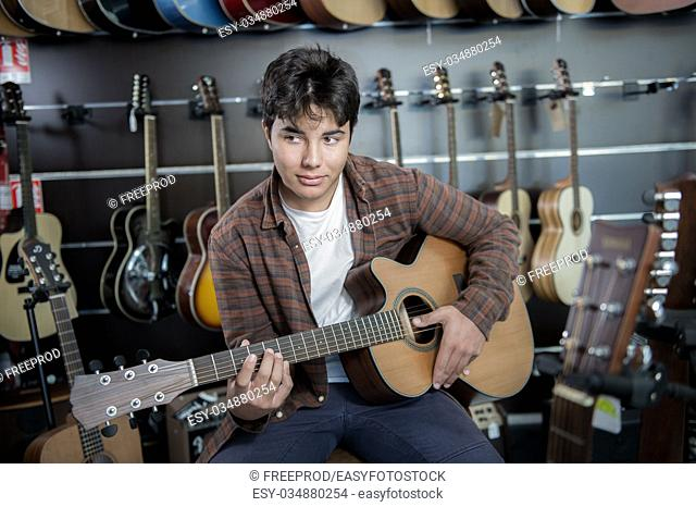 Young man playing the guitar in a shop, France