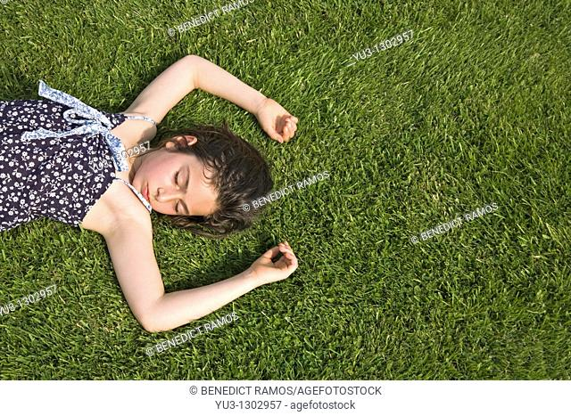 Young girl asleep on grass lawn on a hot summer day