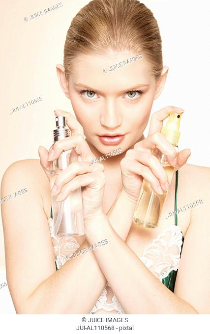Portrait of young woman holding two bottles of perfume