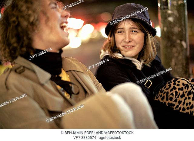 friends sharing funny stories at night in city Berlin, Germany