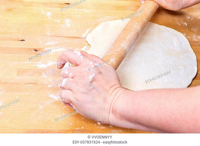 woman rolls out the dough with a rolling pin on wooden table
