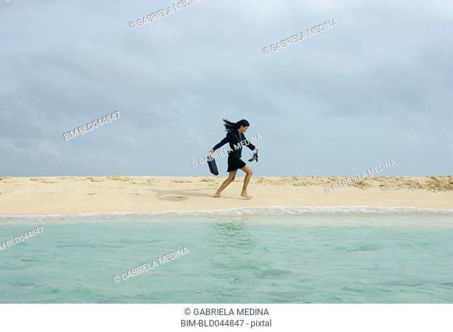 Hispanic businesswoman walking on beach