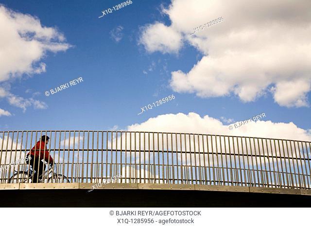 Woman crossing a footbridge on a bicycle  Reykjavik Iceland