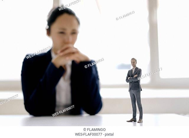 Businesswoman watching businessman figurine, standing on her desk
