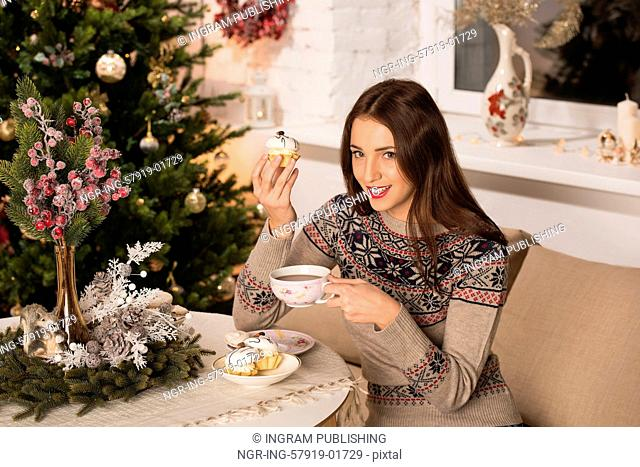 Beautiful woman wearing winter outfit drinking tea with candy at home near Christmas tree