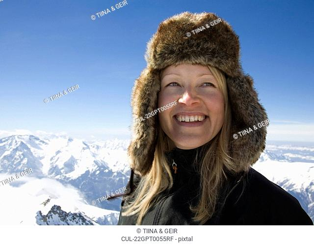 Woman with fur hat on mountain top