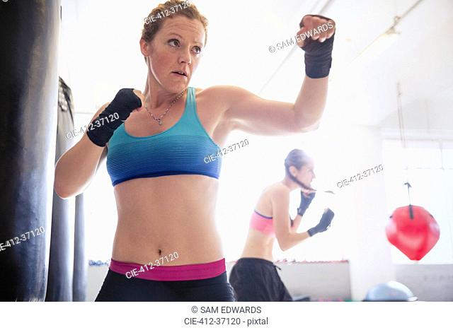 Determined, tough female boxer shadowboxing in gym