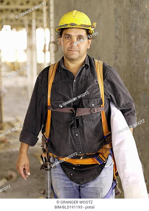 Hispanic worker holding blueprints on construction site