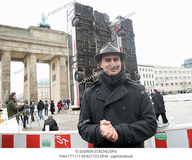 The Syrian artist Manaf Halbouni stands behind the Brandeburg Gate during a press tour for the 3rd Berliner autumn salon of the Maxim Gorki theater