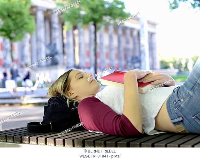 Young woman lying on bench