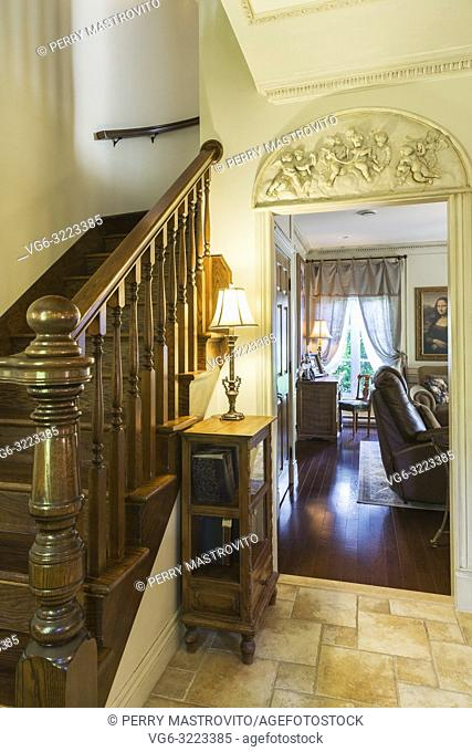 Brown stained oak wood staircase leading to the upstairs floor and living room through doorway inside a 2006 reproduction of a 16th century Renaissance castle...