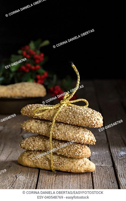 sicilian biscuits with sesame seeds tight with golden bow and decorated with red berries for winter
