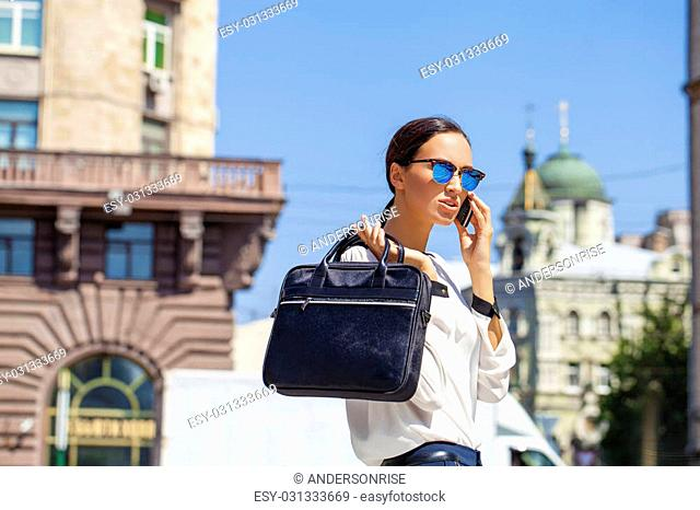 Young beautiful business woman calling by phone, outdoor summer street