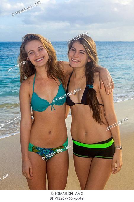 Teenage sisters at the beach; Kailua, Island of Hawaii, Hawaii, United States of America