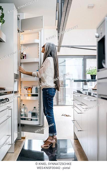 Woman in kitchen looking in fridge