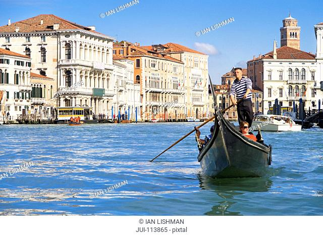 Gondolier paddling tourists in gondola among architectural buildings in sunny Grand Canal in Venice, Italy