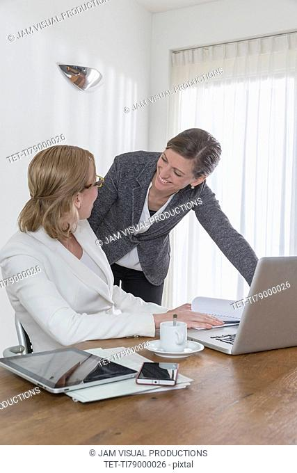 Discussion between businesswomen at work