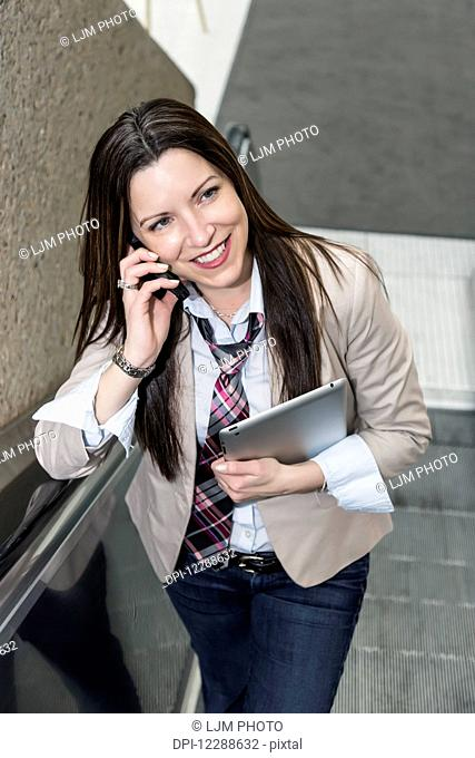 Mature business woman talking on her cell phone and holding a tablet on an escalator in an office building; Edmonton, Alberta, Canada