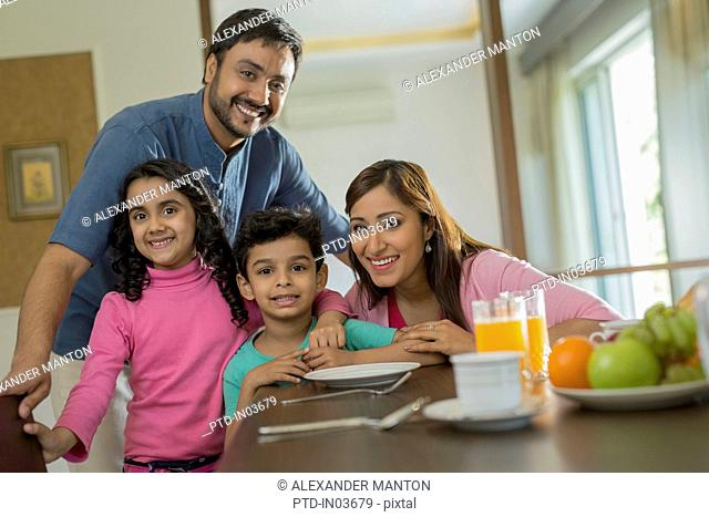 Man and woman with two children at dining table