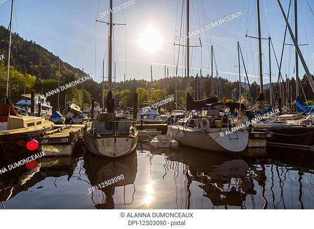 A tranquil sunny afternoon as the sun sets behind the marina at Snug Cove, Bowen Island on the West Coast near Vancouver; Bowen Island, British Columbia, Canada