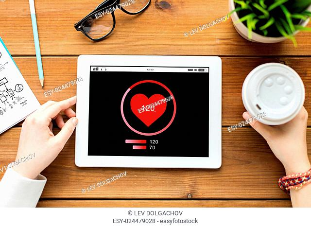 technology, people and healthcare concept - close up of woman with heart rate on tablet pc computer screen and coffee on wooden table