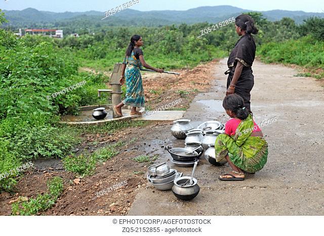 Tribal women cleaning utensils. Birhor tribe. Keredari village and block, District Hazaribagh, Jharkhand, India