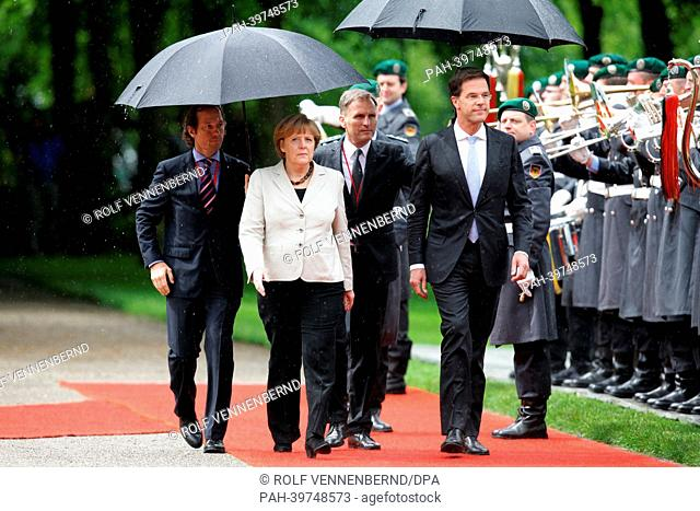 German Chancellor Angela Merkel (C) and Dutch Prime Minister MarkRutte (R) examine the guard of honour before the first German-DutchCabinet Meeting in Kleve