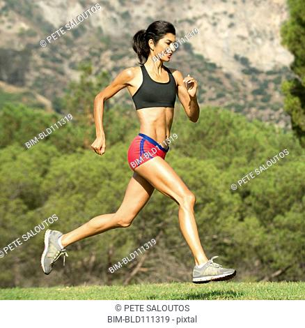 Hispanic woman running in rural field
