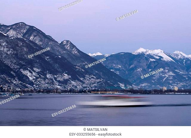Passanger ship in long exposure on a lake with snow-capped mountains in blue hour