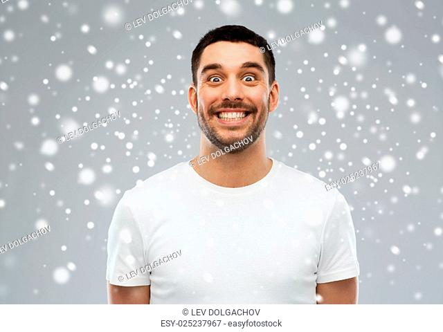 expression, winter, christmas and people concept - man with funny face over snow on gray background