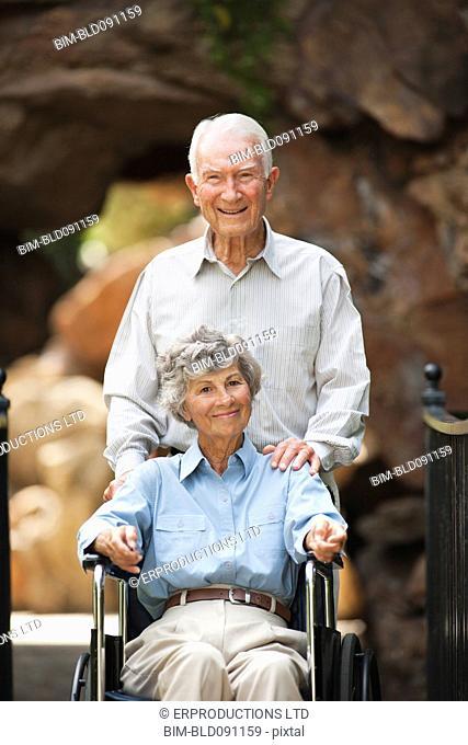 Senior man pushing wife in wheelchair