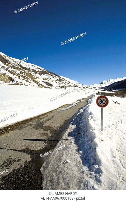 Speed limit sign on snow-covered road