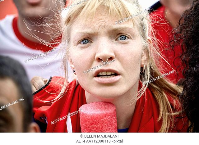 Woman watching football match with furrowed brow, portrait
