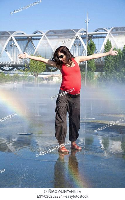 happy pregnant woman dancing in a fountain water