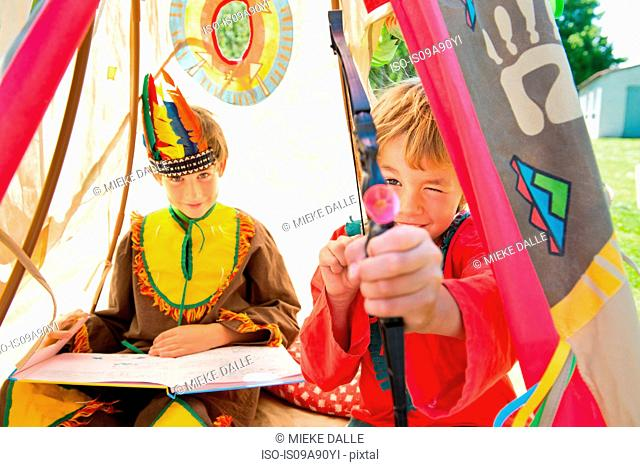 Brothers dressed in Native American costumes playing in teepee, portrait