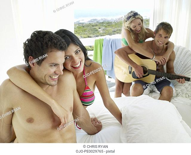 A couple sitting on a bed and another couple with an acoustic guitar