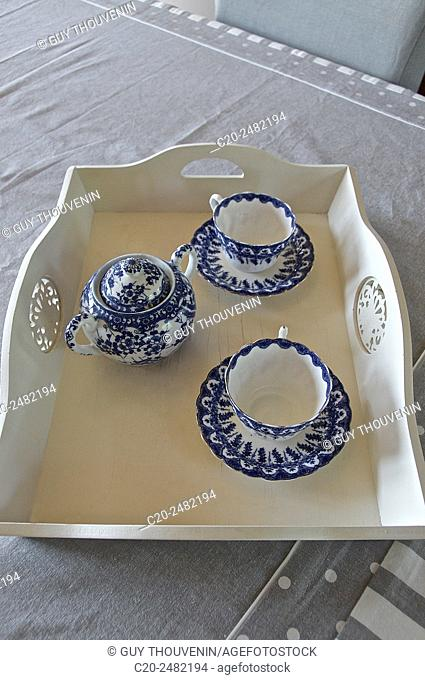 2 blue and white china bone tea cups and sugar bowl on a white wooden tray