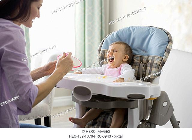 Mother feeding crying baby at home