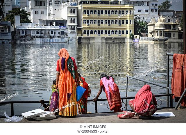 Women in colourful saris standing on the lake shore in Udaipur