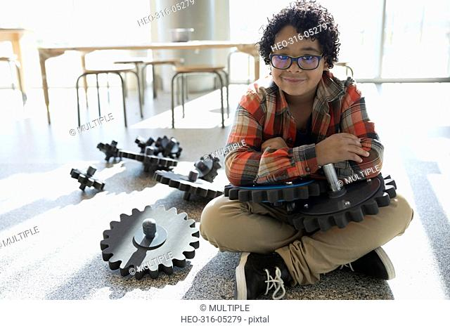 Portrait smiling boy holding cog pieces in science center