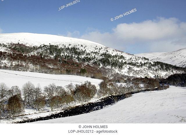 Scotland, Aberdeenshire, Glen Gairn, River Gairn running through the snow covered hills of Glen Gairn