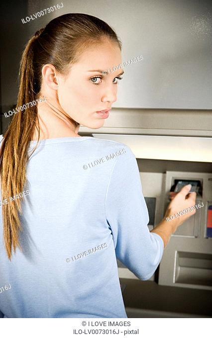 Portrait of a young woman using an ATM cash machine
