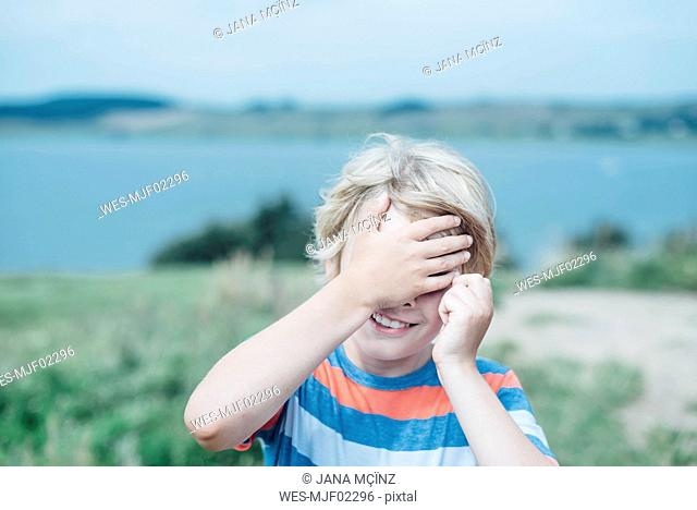 Smiling boy outdoors covering his eyes