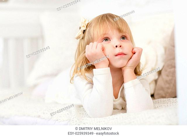 Serious pretty little girl lies on a sofa in the room and looks upwards