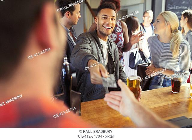 Smiling man paying bartender with credit card at bar