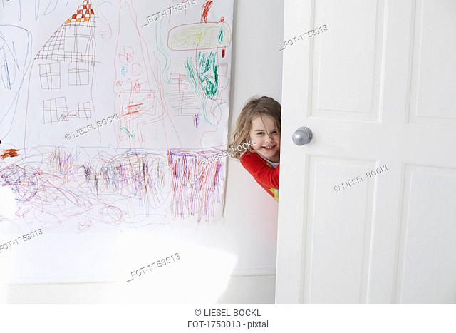 Portrait of cheerful girl hiding behind door against drawing on wall