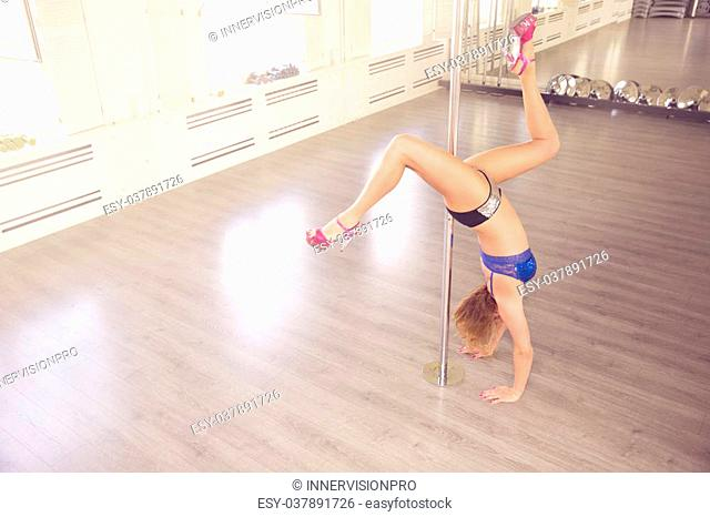 A photo of young woman training on dance pole. She's standing in her hands