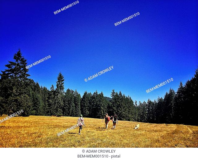People walking with dog in field